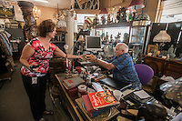 NWA Democrat-Gazette/ANTHONY REYES &bull; @NWATONYR<br /> Lynn Golbeck of Bella Vista talks with Ken Wagner, owner of Ken's Auction, Friday, Sept. 4, 2015 about some antique books at the auction house in Springdale. Golbeck has been visiting and buying from Ken's for years and said she loves coming here. Ken's is having some difficulty with it's business permit on how many and which days he can have his auctions.