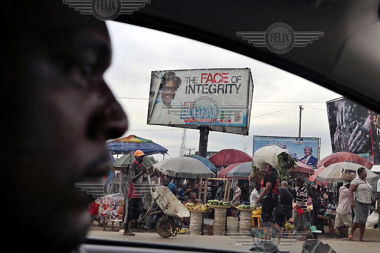 A man drives his car along a street, past an election campaign poster for Buhari, in the oil rich city of Porth Harcourt.