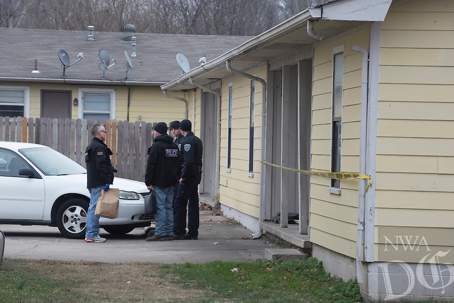 NWA Democrat-Gazette/J.T. WAMPLER John Brooks, crime scene investigator for Fayetteville Police (left) talks to other officers Sunday Dec. 12, 2016 after a shooting at Green Mansion Countryside Apartments at Deane St. and Porter Rd. in Fayetteville. Two people were arrested and one person was hospitalized with a gunshot wound to the hand according to a news release from Fayetteville police.