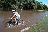 Dave Knecht of Ames rides his bike down University Boulevard Wednesday afternoon in Ames.  Knecht was in Ames for the massive floods of 1993 and said today is comparable to that historic flood.  Flooding in Ames, Iowa Wednesday, August 11, 2010 from the flooded South Skunk River and Squaw Creek.