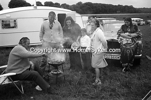 A wealthy gypsies family barbeque, with Rolls Royce and caravan, Derby Day horse race,  Epsom Downs, Surrey, England 1974.<br /> <br /> George James Butcher, sitting at the BBQ.<br /> Lorraine Nethercott leaning against her fathers car.