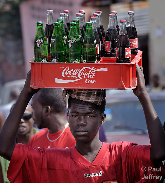 A man carries soft drinks on his head as he walks along a street in Port-au-Prince, Haiti.
