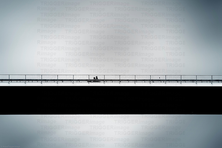 The silhouette of a motorcycle in front of a blurred background, which goes over a bridge.