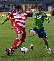 Dallas FC defender George John, left, battles Seattle Sounders FC forward Mike Fucito during play at Qwest Field in Seattle Saturday May 14, 2011. Dallas won the game 1-0.