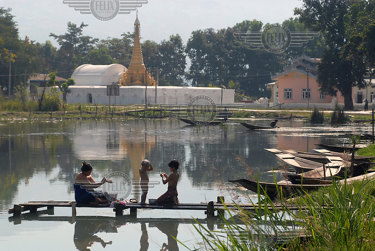 A family washes in a small lake near the main Inle Lake.