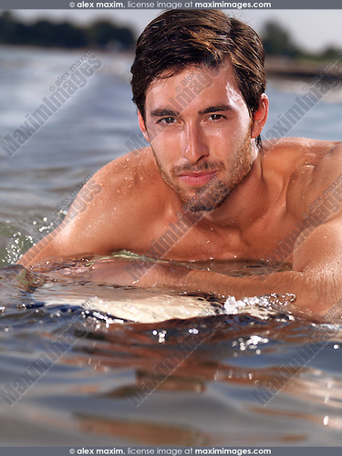 Portrait of a smiling young man with a surfboard in water. Summer lifestyle
