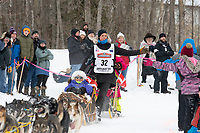Mille Porsild and team run past spectators on the bike/ski trail near University Lake with an Iditarider in the basket and a handler during the Anchorage, Alaska ceremonial start on Saturday, March 7 during the 2020 Iditarod race. Photo © 2020 by Ed Bennett/Bennett Images LLC