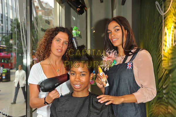 Tara Smith, Tolula Adeyemi & Rosario Dawson.Hollywood hair stylist to the stars (Smith) and her A-list client pose in the window of M&S to launch her new vegan haircare range, Tara Smith Vegan Haircare: Tested on Filmstars Not on Animals. Marks & Spencer Marble Arch, 458 Oxford Street, London, England..September 27th, 2012.half length jacket blouse skirt black yellow beige white top trousers red white pink sitting cape apron blowdryer dryer.CAP/CJ.©Chris Joseph/Capital Pictures.