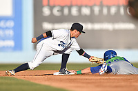 Asheville Tourists shortstop Jose Gomez (4) fields the ball and tags out a hard sliding John Brontsema (15) during a game against the Lexington Legends  at McCormick Field on May 31, 2017 in Asheville, North Carolina. The Tourists defeated the Legends 12-5. (Tony Farlow/Four Seam Images)