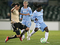 FC Gold Pride's Christine Sinclair (12)  jumps in to tackle the ball away from Sky Blue's Anita Asante (5).  Sky Blue FC and FC Gold Pride battled to a 1-1 draw in Bridgewater, NJ on Saturday, April 11, 2009.