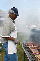 A chef grills brats during Badgers tailgating on Saturday, October 12, 2013 in Madison, Wisconsin
