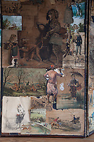 A detail of a Victorian decoupage screen, which has been decorated with amusing scenes and caricatures, now peeling and damaged