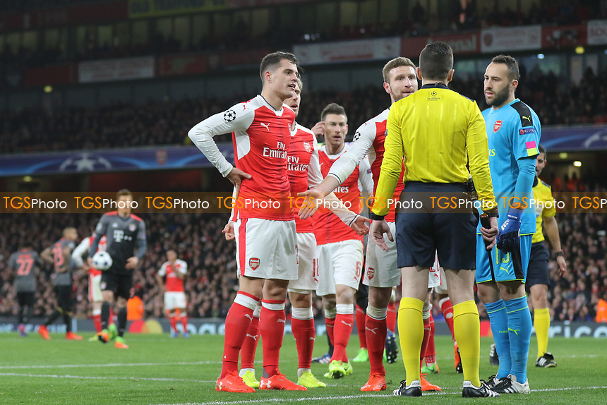 Arsenal's Granit Xhaka and Shkodran Mustafi speak to the Referee's assistant  next to the goal after he seemed to influence Referee, Tasos Sidiropoulos, to show Arsenal's Laurent Koscielny, a red card during Arsenal vs FC Bayern Munich, UEFA Champions League Football at the Emirates Stadium on 7th March 2017