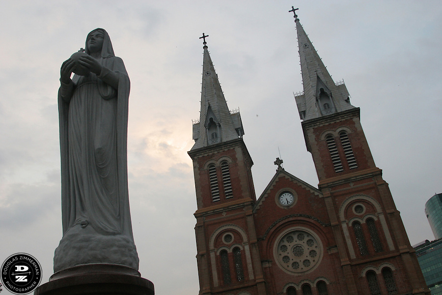 A statue of the Virgin Mary stands outside the Notre Dame Cathedral in the heart of Ho Chi Minh City's government quarter in Ho Chi Minh City, Vietnam.  The neo-Romanesque cathedral was completed in 1883.  Photograph by Douglas ZImmerman