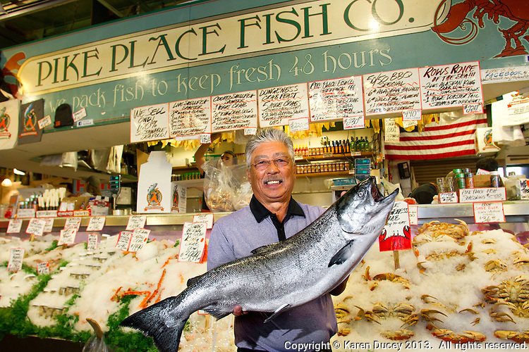 John Yokoyama, owner of Pike Place Fish Market holds a wild-caught King salmon from Alaska in Seattle, Wash., on July 1, 2013.  Yokoyama has owned the market since 1965.(photo © karenducey.com)
