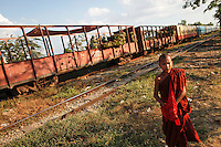 A Buddhist novice monk walks past railway tracks as a train passes by in Yangon's suburbs December 2, 2011. Pro-democracy leader Aung San Suu Kyi welcomed on Friday renewed U.S. engagement with Myanmar, saying she hoped it would set her long-isolated country on the road to democracy.  REUTERS/Damir Sagolj (MYANMAR)
