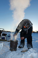 Justin Savidis thaws his water drink in his dog water at sunrise and 20 below zero weather at the ghost-town checkpoint of Iditarod on Friday morning during the 2011 Iditarod race..