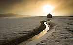 Idaho, North, Panhandle, Worley. Farmland covered in snow and a seasonl  ditch with ice reflect the morning sun as it burns through fog.