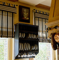 A plate rack hangs between a pair of windows which are dressed with black and white striped Roman blinds