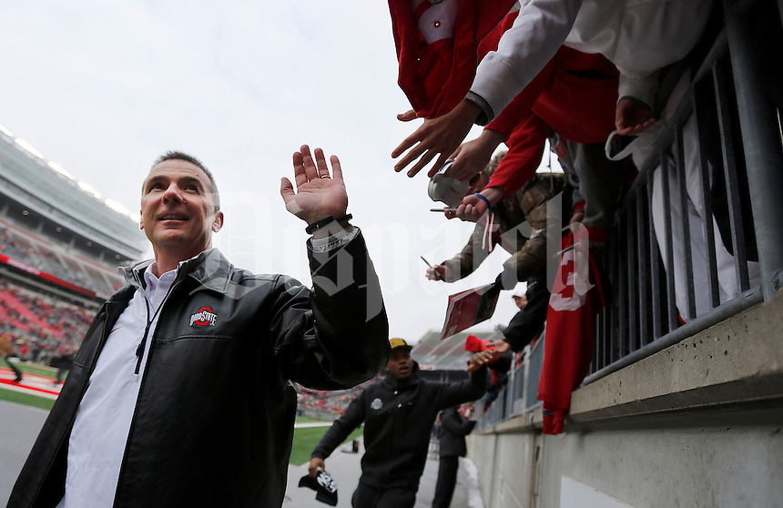Head coach Urban Meyer gives high fives while leaving the stadium after the Ohio State football National Championship celebration at Ohio Stadium on Saturday, January 24, 2015. (Columbus Dispatch photo by Jonathan Quilter)