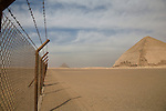 Rusty military fencing surrounding the Bent Pyramid and the Red Pyramid, located 10km south of Saqqara in Dahshur, Egypt.