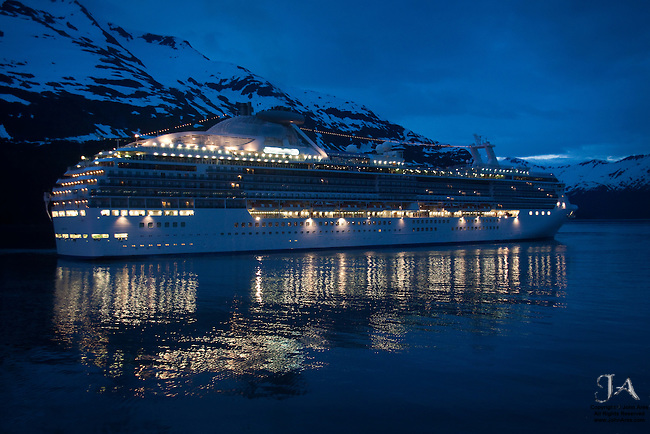 Cruise ship at night, lit up with dramatic mountains behind in Whittier, Alaska.  Shot through the hotel window.