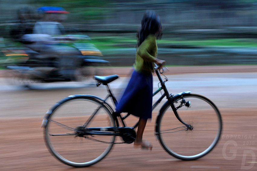 A local Khmer Girl on a bike passes by the Bayon Temple, Activity near he popular Bayon temple ruins