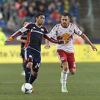 New England Revolution midfielder Lee Nguyen (24) brings the ball forward as New York Red Bulls midfielder Eric Alexander (12) pressures. In a Major League Soccer (MLS) match, the New England Revolution (blue) tied New York Red Bulls (white), 1-1, at Gillette Stadium on May 11, 2013.