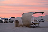 Vintage, curved picnic shelters are seen in a parking area as the sun sets at White Sands National Monument near Alamogordo, New Mexico, USA, on Sat., Dec. 30, 2017.