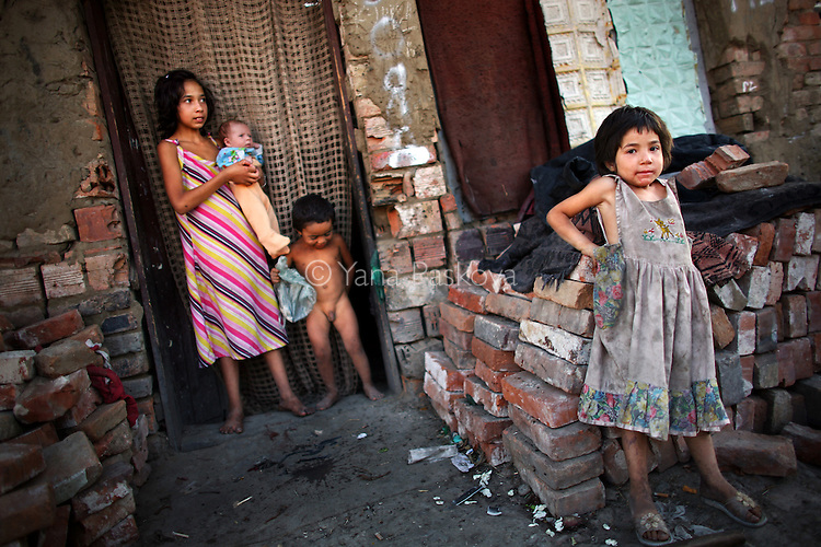Children lean against an unfinished house in a Roma village in Northwest Bulgaria in August 2008.