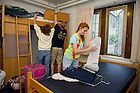August 17, 2012; Freshman Casey Skevington unpacks as her parents, Susan and Ed work on her bunk bed in her dorm.  Photo by Barbara Johnston/University of Notre Dame