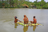 A family cross the floodwaters on a raft made from banana trees. Thousands of people were displaced in Shyamnagar Upazila, Satkhira district after Cyclone Aila struck Bangladesh on 25/05/2009, triggering tidal surges and floods..