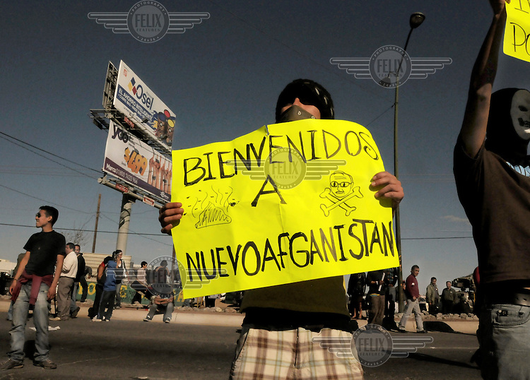 A demonstrator protests the visit of Mexican President Calderon to Cuidad Juarez. He holds a poster which reads: 'Welcome to New Afghanistan'. Ciudad Juarez has become the world's most dangerous city. More than 2600 people were killed in 2009. Since President Calderon declared war on the drugs cartels in 2006 and deployed thousands of troops, the violence has only increased.