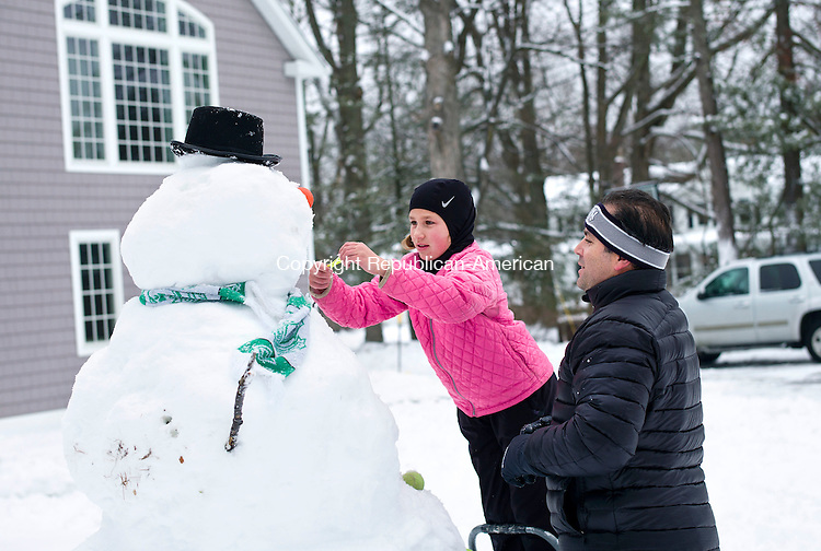 Middlebury, CT- 17 December 2016-121716CM01-  Vinnie Graziano and his daughter, Faith 10, put the finishing touches on a snowman outside their home in Middlebury on Saturday.   Faith said she had built a smaller snowman, then decided to make a much larger one.  Standing over 6 feet tall, she said it took them about an hour to complete.  The snowman featured lacrosse balls as eyes, tennis balls as buttons and a candle for a nose.    Christopher Massa Republican-American