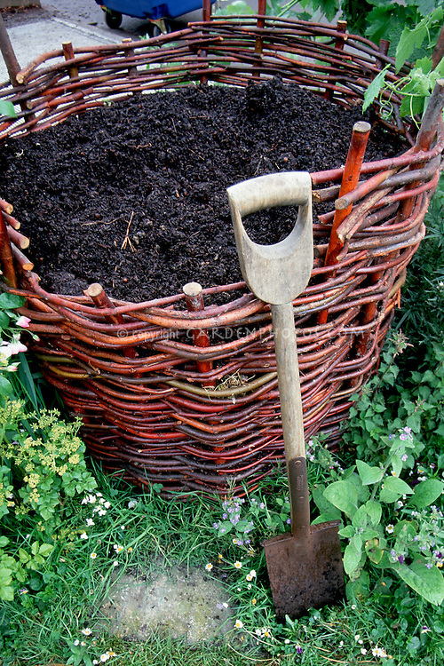 Compost Bin woven of wicker, with garden shovel and finished compost