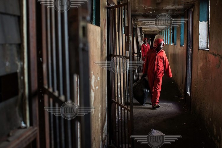 A member of the Red Ants walks along a corridor in Fatti's Mansions on Jeppe Street during an operation to clear the block of its illegal occupants. The Red Ants are a controversial private security company often hired to clear squatters from land and so-called 'hijacked' properties.