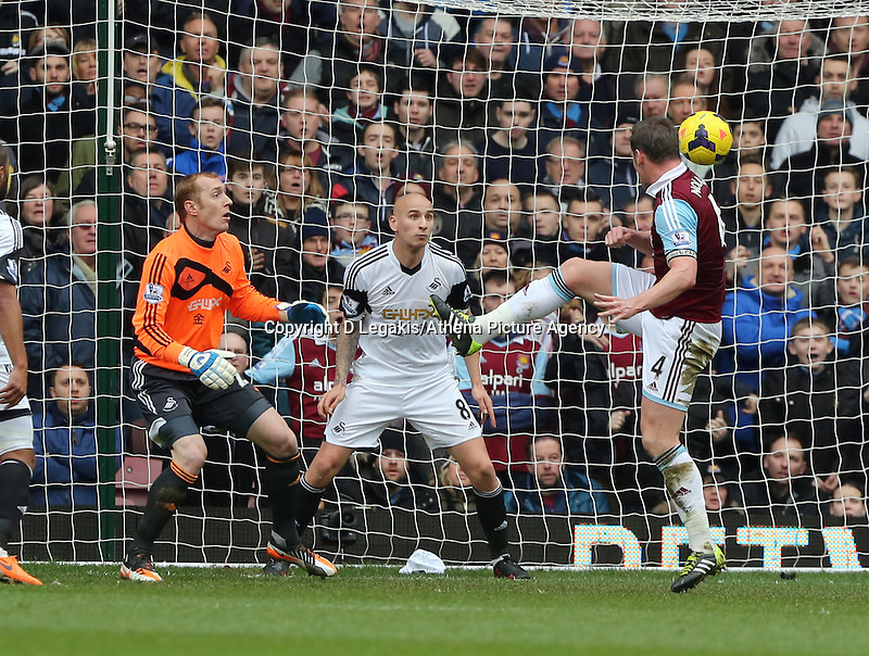 Pictured L-R: Swansea goalkeeper Gerhard Tremmel and team mate Jonjo Shelvey look on as Kevin Nolan of West Ham scores his second goal. 01 February 2014<br /> Re: Barclay's Premier League, West Ham United v Swansea City FC at Boleyn Ground, London.