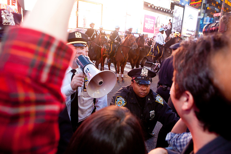 """Police officers threaten protesters with """"Occupy Wall Street"""" with arrest at Times Square on October 15, 2011 in New York City.  While crowd estimates numbered in the tens of thousands, police tactics (including nets, motor scooters, barricades, arrests, and intimidation by riders on horseback) prevented the crowd, which had been split up, from joining together as one in the middle of Times Square."""