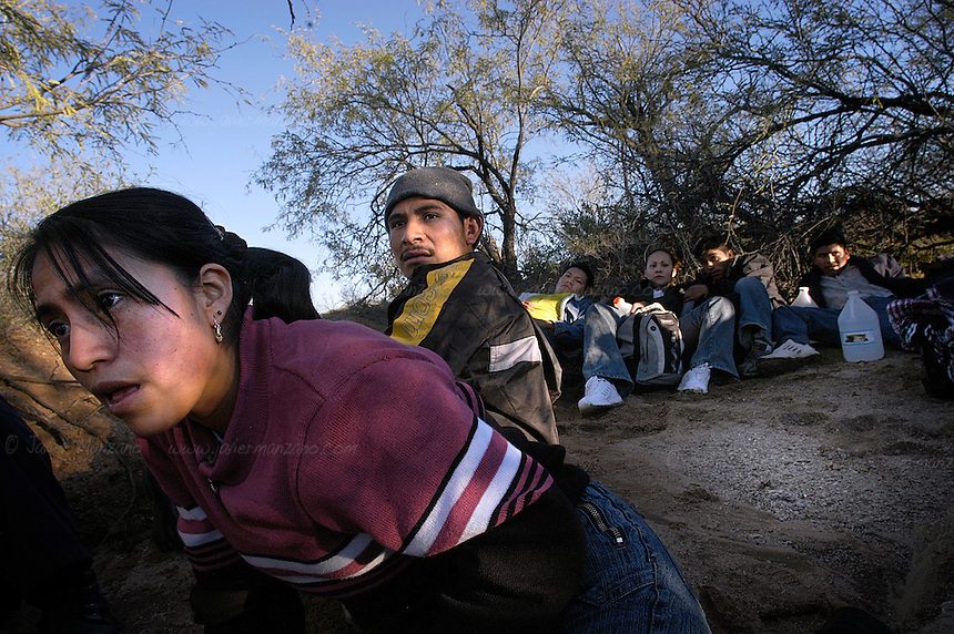Central American men and women bound for the border take cover from a border patrol vehicle, patrolling alongside the border with Sonora, Mexico. This group of 37 border-crossers, take cover in the many dried-up river beds that parallel the border, as they wait for the cover of darkness to make their way through the wire fence that separates both countries. .      .Sonora-Mexico. 01/28/05.