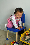 Oakland CA Fourteen-month-old girl having a tantrum because she's stuck on a chair