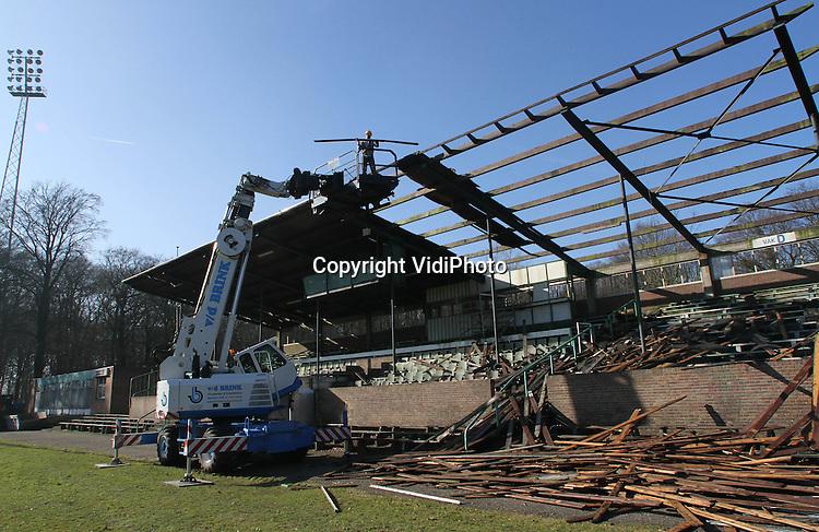 Foto: VidiPhoto..WAGENINGEN - Het dak gaat er af. Letterlijk ditmaal. In stadion de Wageningse Berg is donderdag door sloopbedrijf G. E. van Dam uit Rhenen begonnen met de sloop van het dak op de hoofdtribune. Sinds voetbalclub FC Wageningen in 1992 failliet ging, is het oude stadion nauwelijks onderhouden. Het houten dak op de hoofdtribune zorgt nu voor een gevaarlijke situatie. Fans van FC Wageningen hopen dat de sloop het begin is van een nieuwe start. Er zijn plannen voor een nieuw multifunctioneel sportcentrum in het stadion. .