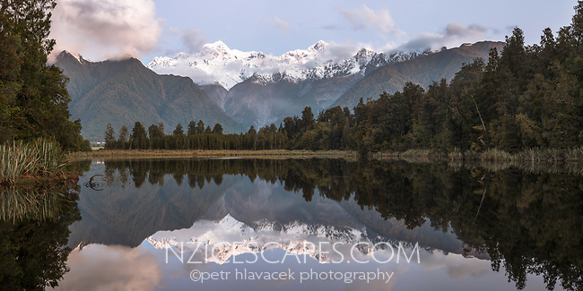 Sunset at Lake Matheson with Aoraki Mount Cook and Mount Tasman of Southern Alps, Westland Tai Poutini National Park, UNESCO World Heritage Area, West Coast, New Zealand, NZ