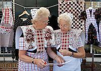 SPAKENBURG  -  Elk jaar vinden in de zomer de Spakenburgse Dagen plaats. Vier woensdagen met folkloristische activiteiten . Vrouwen in klederdracht staan achter een kraampje op de markt