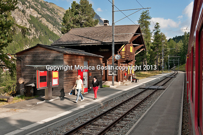 Swiss red Bernina Express trains stop at Surovas train station, on the way to St. Moritz, Switzerland