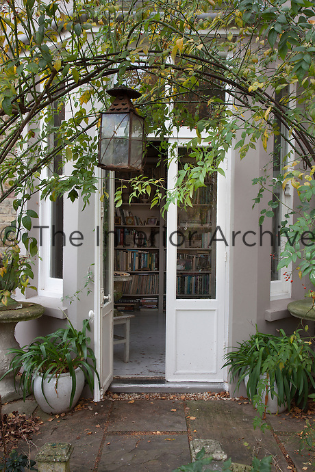 View into the library through French windows framed by a leafy arch