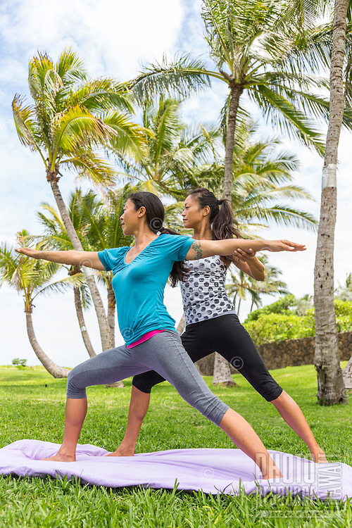 Yoga instructor Miki Sato assists a student with yoga asana at beach park on O'ahu.