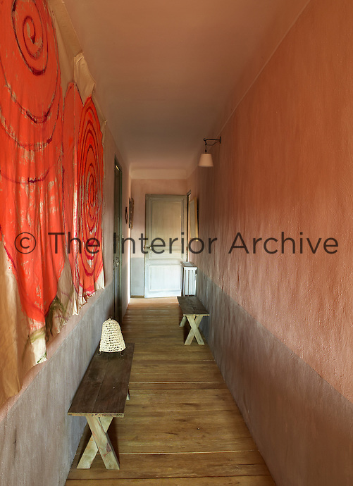 Red-painted wall hangings line one side of this corridor while the other is painted in a duo-tone