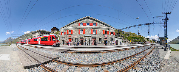 Train of Rhätische Bahn arriving at Ospizio Bernina railway station on the Berninapass. Switzerland, Western Europe, Graubünden, Bernina, UNESCO World Heritage site Rhaetien Railway. Note: This is a digitally stitched panoramic image. No releases available. --- Info: Part of the Rhaetian Railway the Bernina Railway is a single track metre gauge railway. It links St. Moritz, in the Canton of Graubünden, Switzerland, with the town of Tirano, in the Province of Sondrio, Italy, via the Bernina Pass and was fully opened in 1910. From the beginning, the line was electrically operated. It also ranks as the highest adhesion railway in the Alps, and with inclines of up to 7 percent as one of the steepest adhesion railways in the world. In 2008, the Bernina Railway and the Albula Railway were recorded in the list of UNESCO World Heritage Sites, under the name Rhaetian Railway in the Albula / Bernina Landscapes. The whole site is regarded as a cross border joint Swiss-Italian heritage area. The most famous trains operating on the Bernina Railway are known as the Bernina Express.