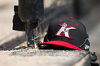 A Kannapolis Intimidators cap sits on top of a glove in the home dugout during the game against the West Virginia Power at Kannapolis Intimidators Stadium on June 18, 2017 in Kannapolis, North Carolina.  The Intimidators defeated the Power 5-3 to win the South Atlantic League Northern Division first half title.  It is the first trip to the playoffs for the Intimidators since 2009.  (Brian Westerholt/Four Seam Images)