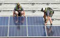 NWA Democrat-Gazette/DAVID GOTTSCHALK Kyle Shaw (left) and Mitchell Hooe (cq), crew lead, both with Shine Solar of Bentonville, position solar panels Monday, May 14, 2018, on the roof of the Good Shepherd Lutheran Church in Fayetteville. Two hundred and fifty two panels measuring 39 inches by 70 inches are being placed on the support rails that will be part of a 90 kilowatt power system.